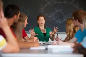 Woman addressing table of seated students listening