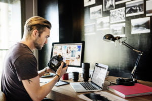 Man transferring photos from camera to computer