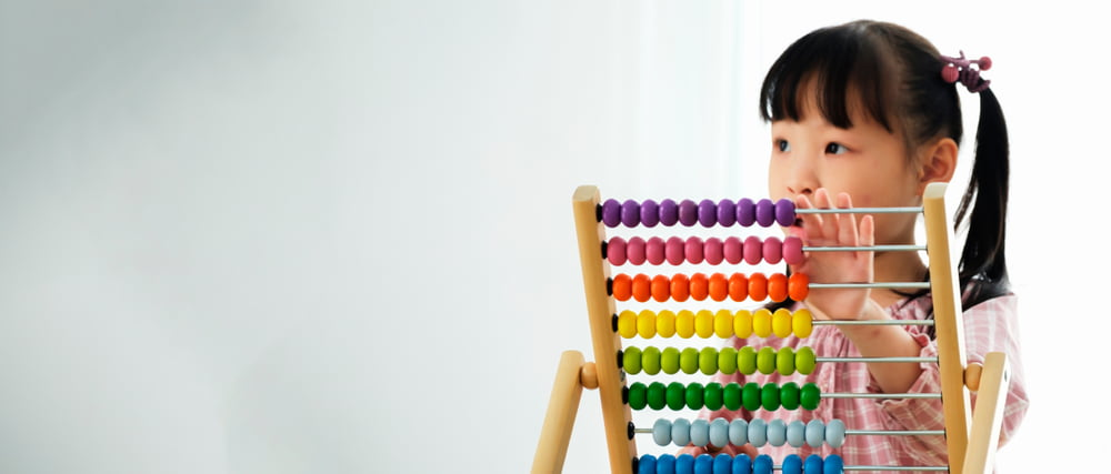young child with abacus image for early childhood education degree online
