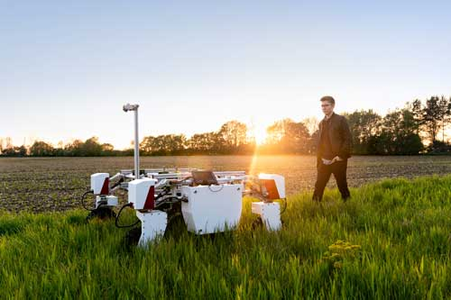 mechanical engineer with sustainable agricultural robot in field